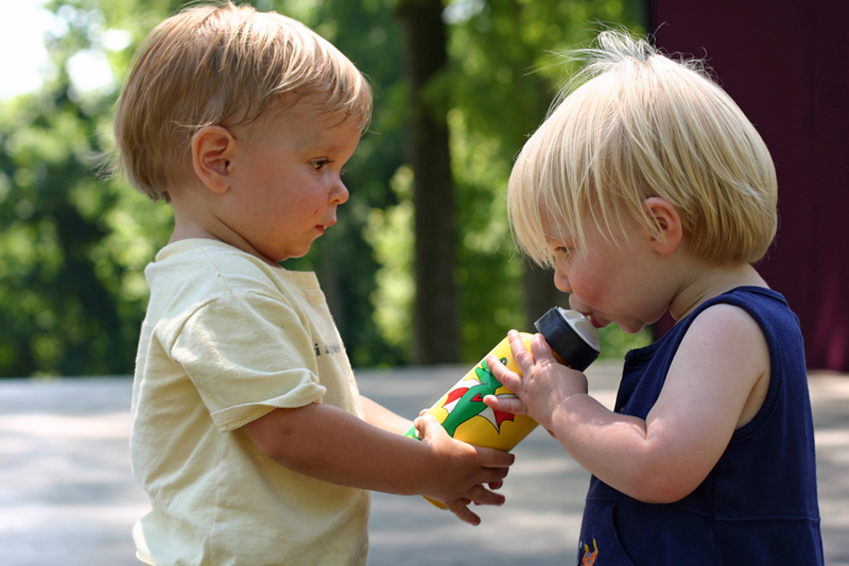 Two toddlers sharing a sippy juice
